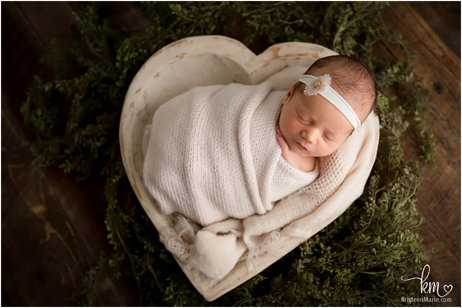 sleeping newborn in heart bowl