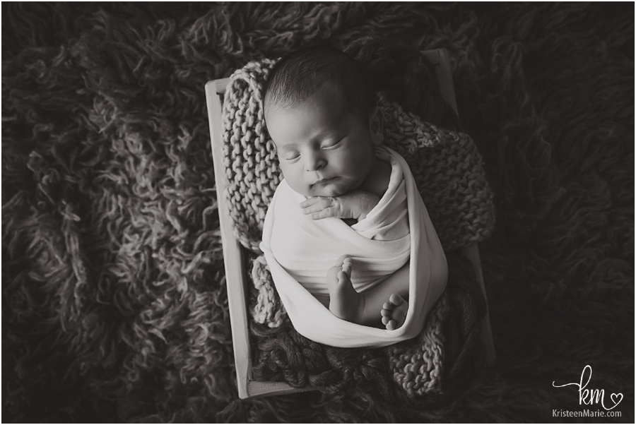 black and white image of newborn baby wrapped