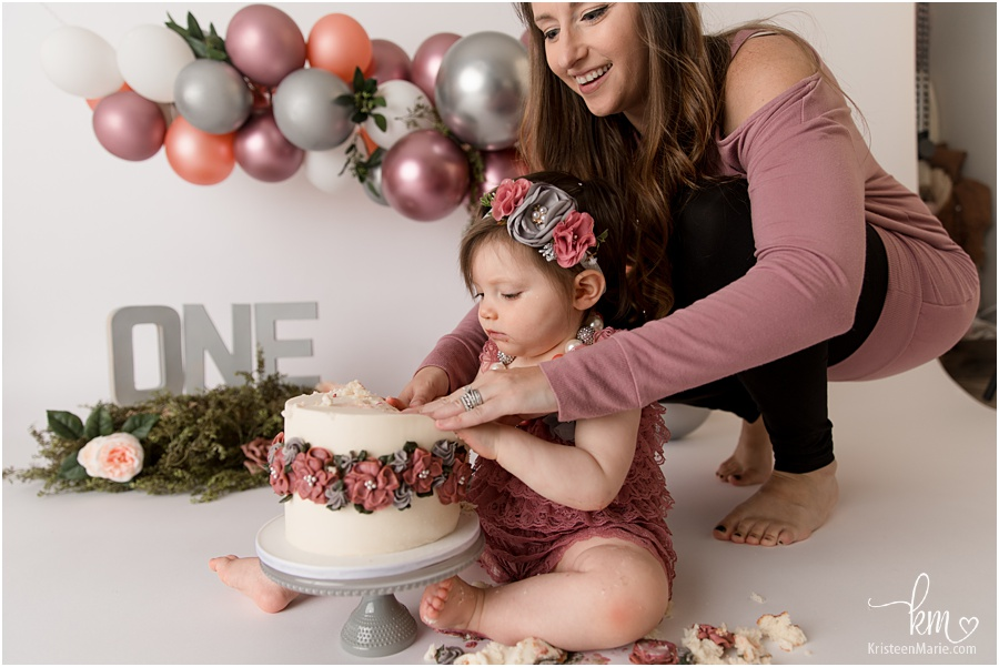 mom helping baby with smash cake