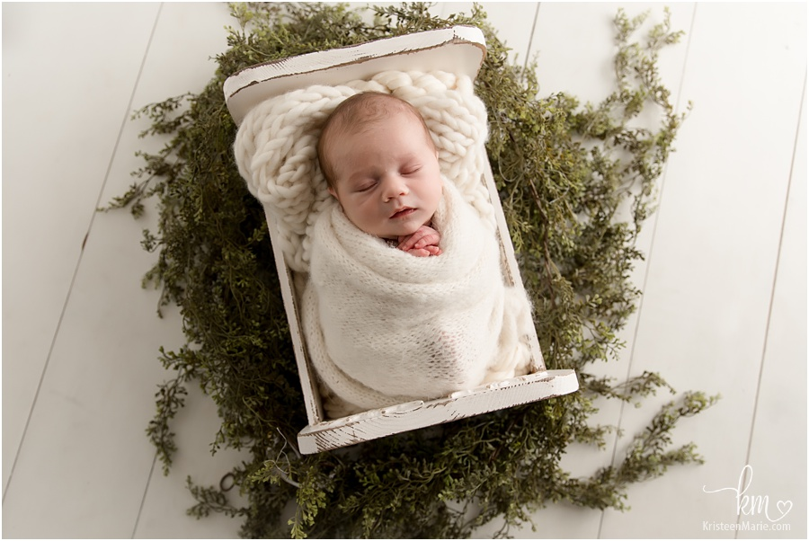sleeping newborn boy with greenery