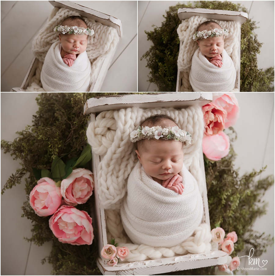 newborn baby in white whith greenery and flowers