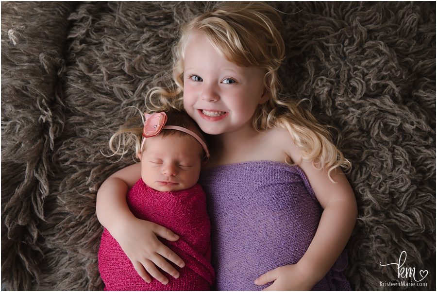 newborn baby girl with sister in photography studio in Indianapolis