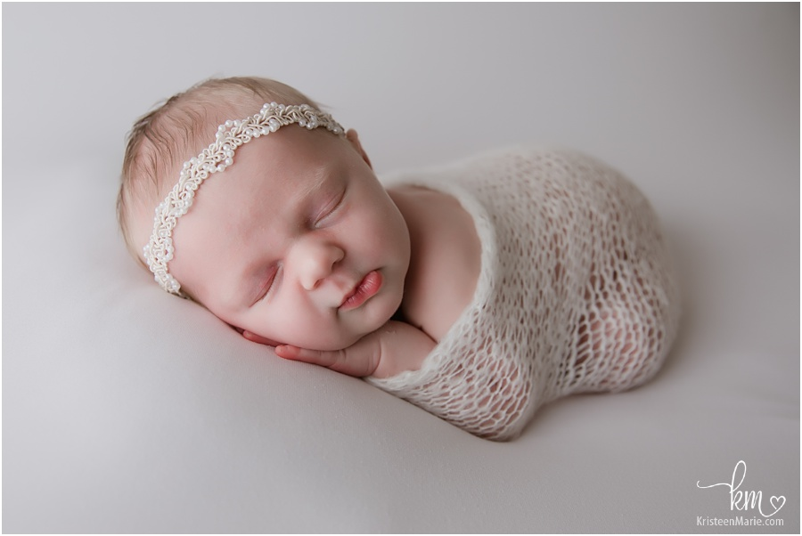 newborn baby girl on white backdrop