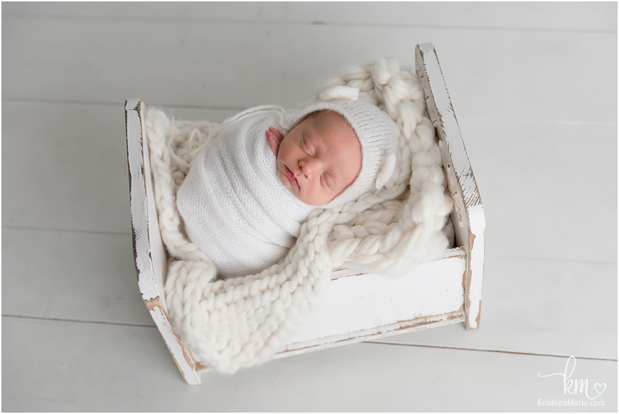 sleeping newborn boy in wood crib prop