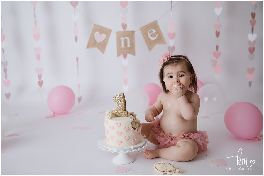 baby girl eating cake for 1st birthday