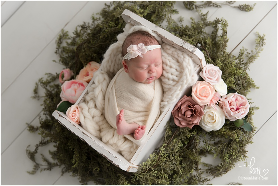 newborn baby girl with blush and pink flowers and greenery