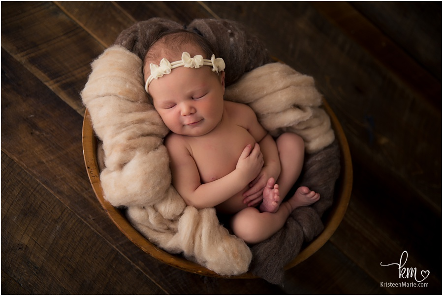 newborn baby girl in bowl and bow in hair