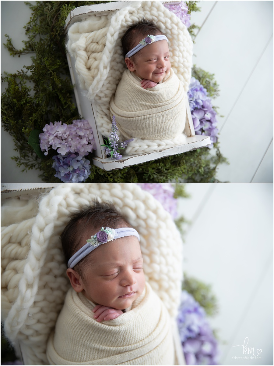 newborn baby girl smling surrounded by purple flowers