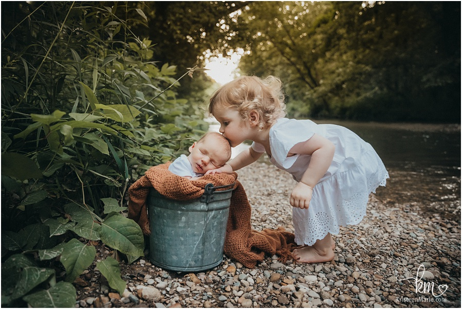 outdoor newborn picture with siblins - baby in a bucket with big sister kissing